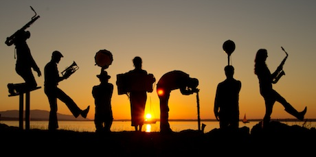 A silhouette of the members of Skitnik spelling Sitnik with their bodies and instruments